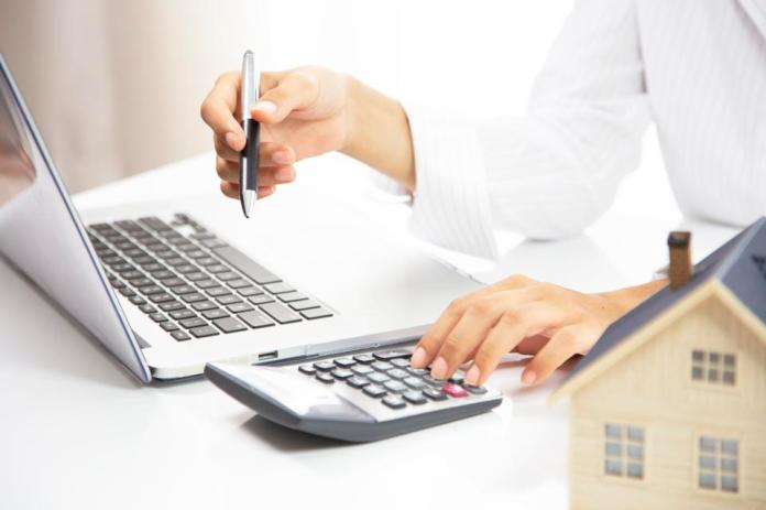 Business woman hands working on calculator with working laptop