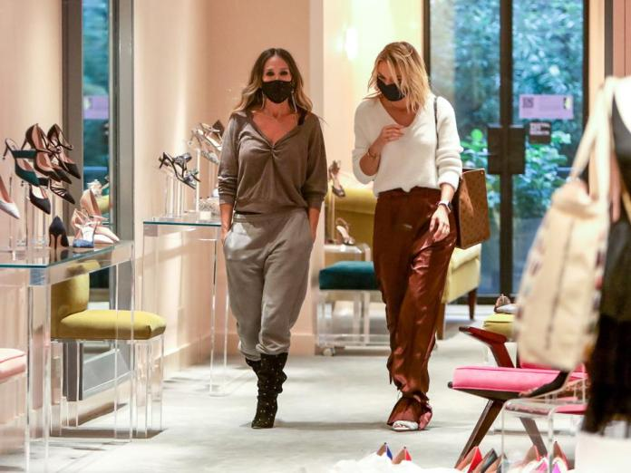 Sarah Jessica Parker helps model Irina Baeva  try on shoes at her new East 54th SJP shoe store in New York City.