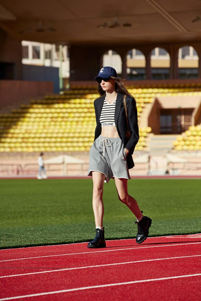 A model on a stadium used as a runway in grey sweat short, striped crop top, blazer and baseball cap