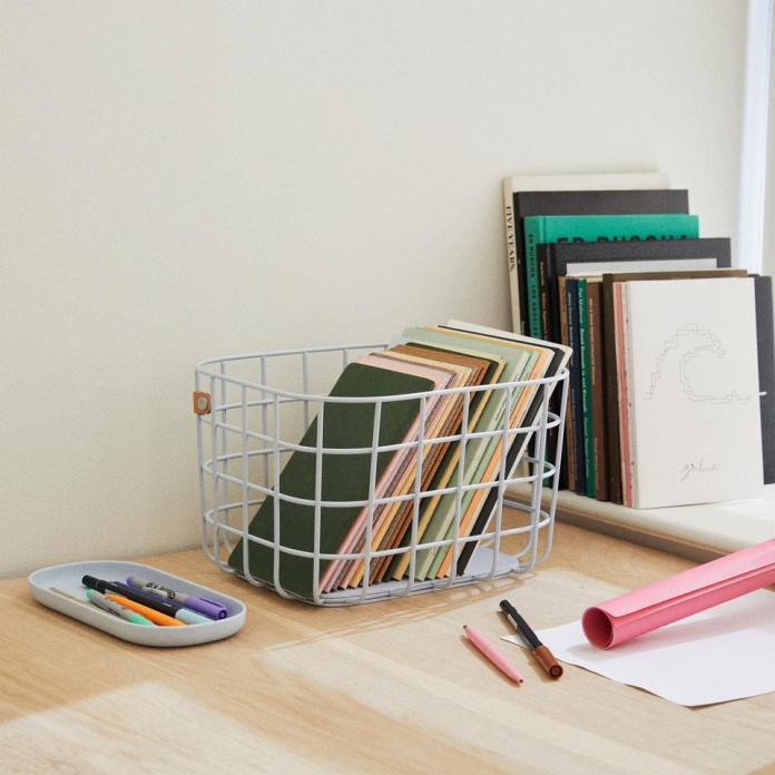 A tidy desk showcasing Open Spaces' white wire basket containing slim books