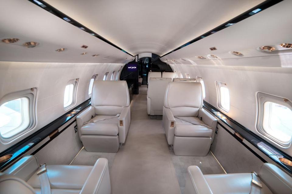 El interior de un jet privado con amplios asientos.