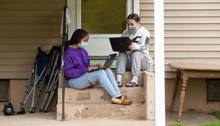 Two girls sitting on back steps wearing face masks and working on laptop computers.