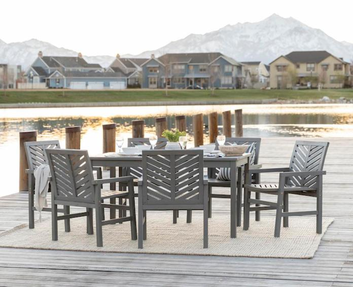 outdoor furniture by water with mountains in the background