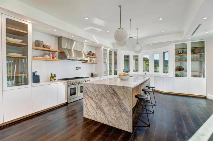 A kitchen with a center island and custom cabinetry.