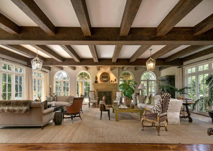 The grand living room has three walls of windows, a beamed ceiling and a central fireplace.