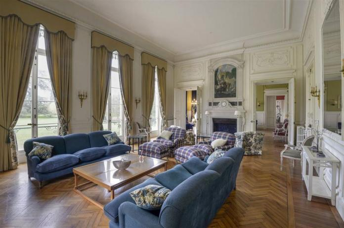 The ornate living room has high ceilings, herringbone patterned wood floors, and a fireplace.