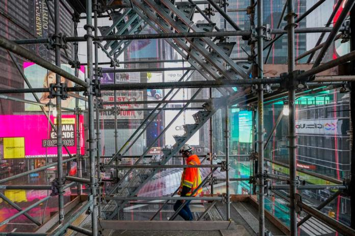 One construction worker walking on a staircase in the scaffolding of TSX Broadway