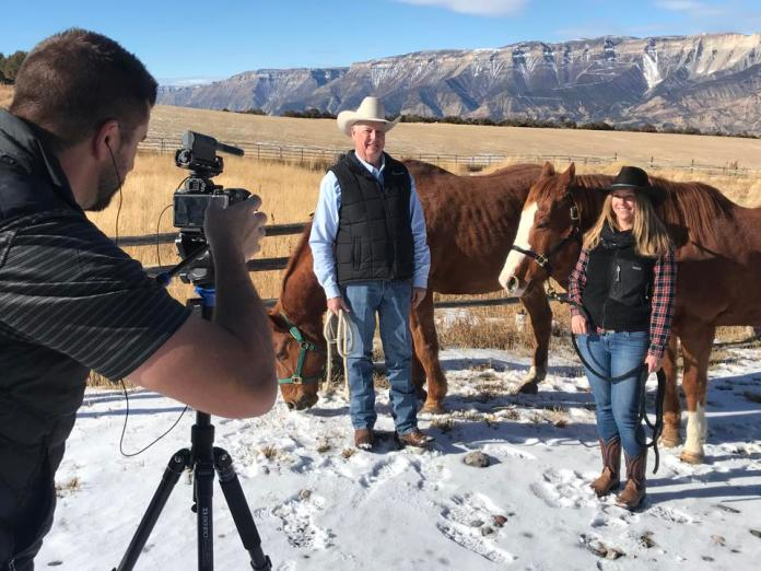 Camera operator Matthew Rollins interviews a man and a woman standing with horses in the snow against a backdrop of mountains.