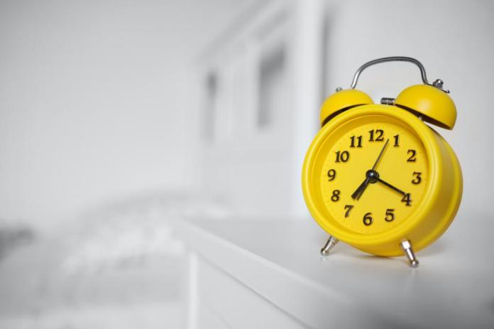 Pantone Color of the Year 2021: Ultimate Gray and Illuminating. yellow alarm clock standing on nightstand in background of bed in interior of room.