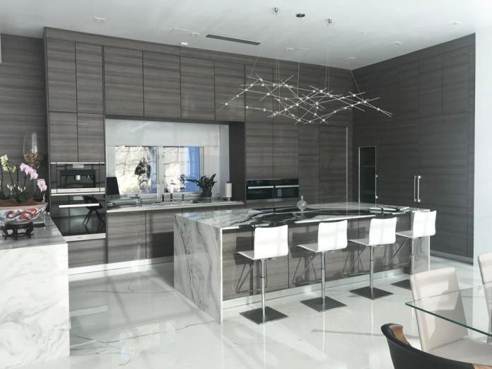 Kitchen with grey laminate cabinetry and marble look countertops and flooring.