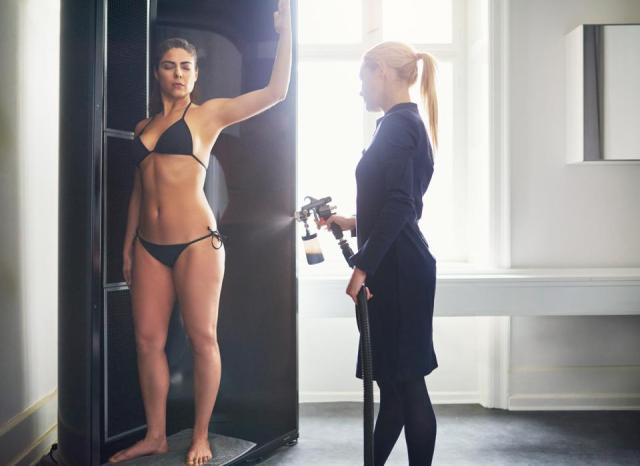 Cosmetologist applying spray tan on woman in salon