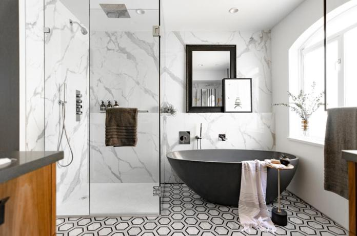 Black and white bathroom with deep tub and large shower.