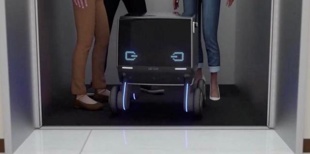 Delivery robot with smiling eyes riding elevator with passengers