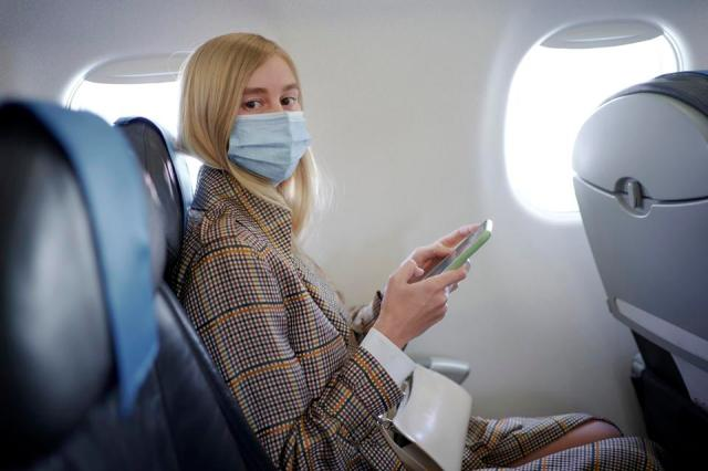 Woman wearing mask inside airplane