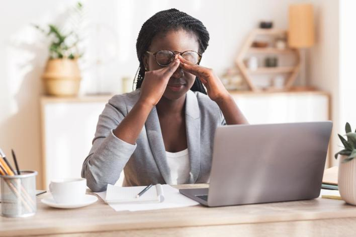 Overworked Black Businesswoman Massaging Nosebridge At Workplace Having Eyesight Problem