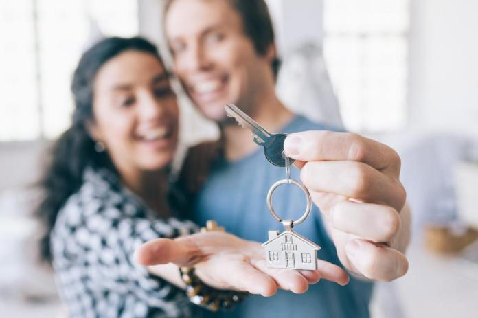 Couple cheerful home owners holding a key