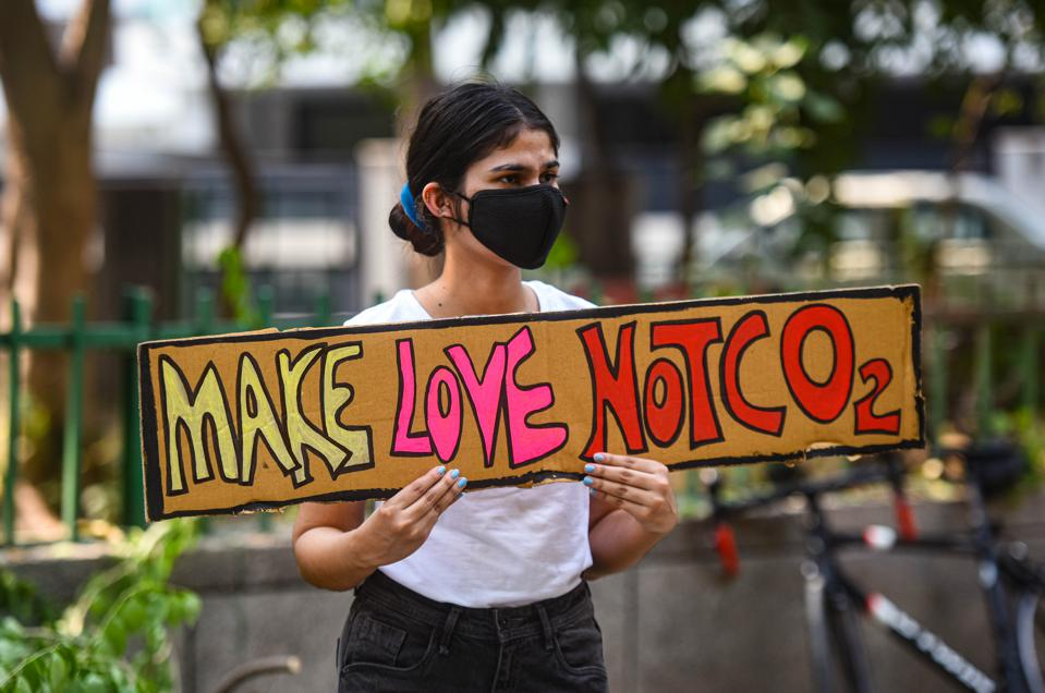 An activist holds a placard reading ″Make love not CO2″ at a protest in New Delhi, India.