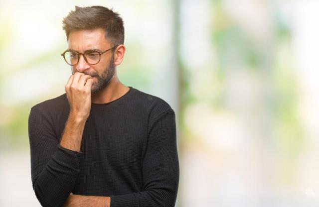Adult hispanic man wearing glasses over isolated background looking stressed and nervous with hands on mouth biting nails. Anxiety problem.