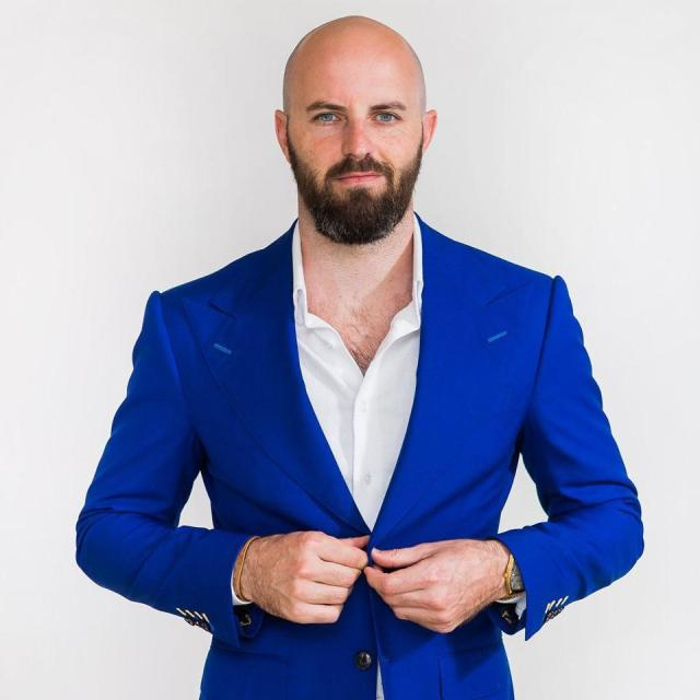 Man in a blue suit staring at camera