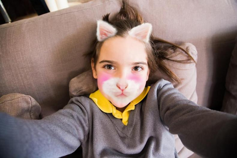 Little girl using smartphone application changing her face with kitten face.