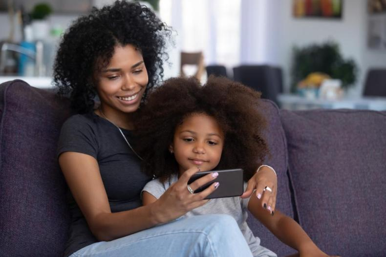 Mixed-race mom and child girl making video call on cellphone.