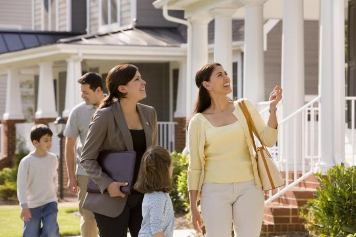 Real estate agent showing house to young family