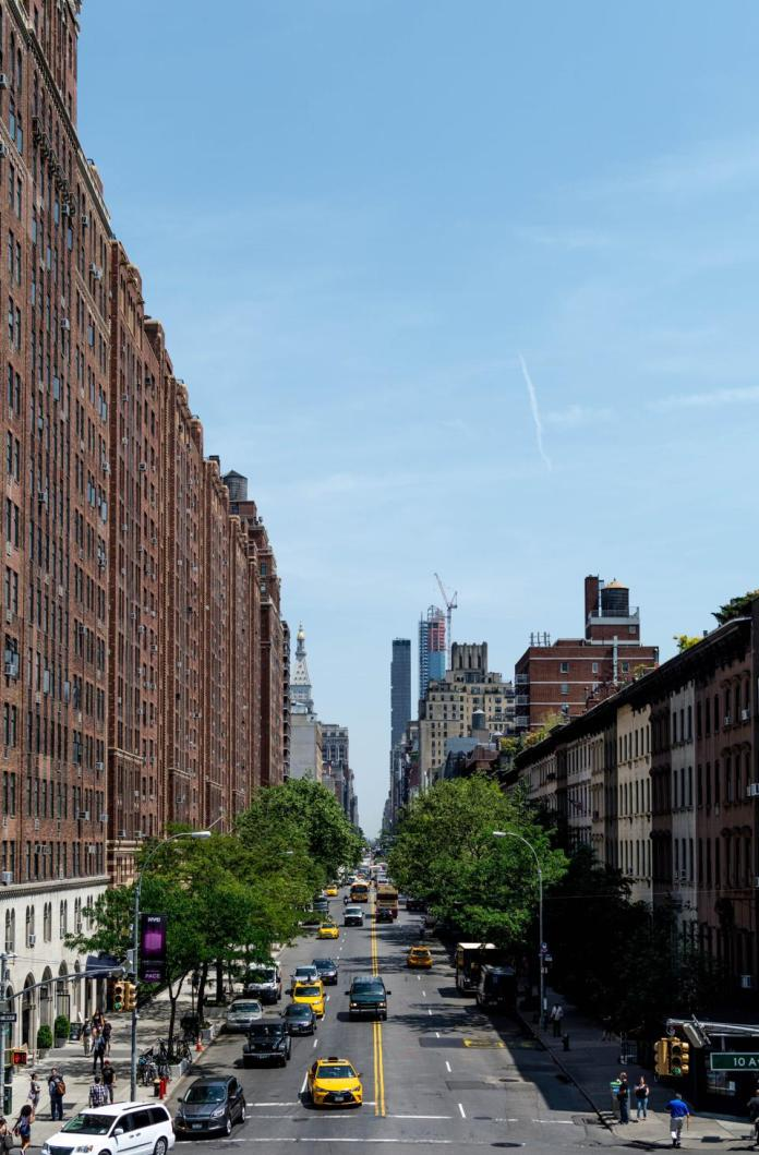 The view up an NYC avenue in the daytime with moderate traffic.