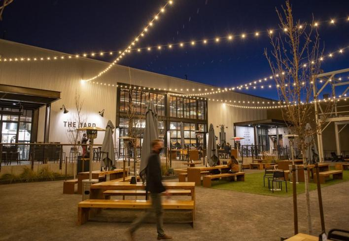 There are outdoor tables under lights at the Sawmill Market in Albuquerque, New Mexico