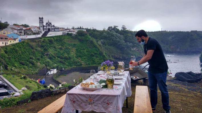 A sommelier pours wines at a table in front of a church and a bay in São Miguel, Azores