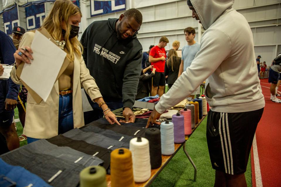Ole Miss football student athletes choosing their fabrics and thread colors for custom jeans from Blue Delta Jeans
