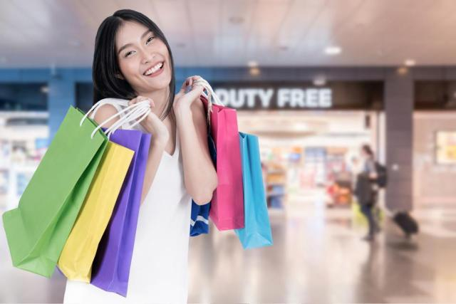 Beautiful Asian woman with shopping bags in duty free in International airport before departure. Sale, shopping, tourism.
