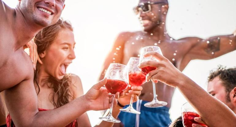 Happy friends drinking sangria wine at exclusive boat party - Young people having fun in summer vacation - Focus on left man hand glass - Travel, friendship, holidays and youth lifestyle concept
