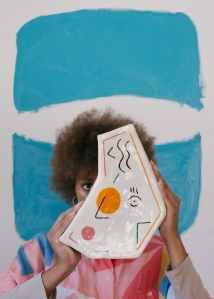 creative female artist with painted vase in modern studio