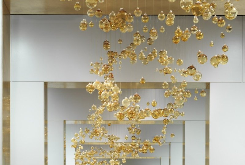 Top. Over 5000 golden baubles have each been hand strung and hung in the art gallery inspired showroom