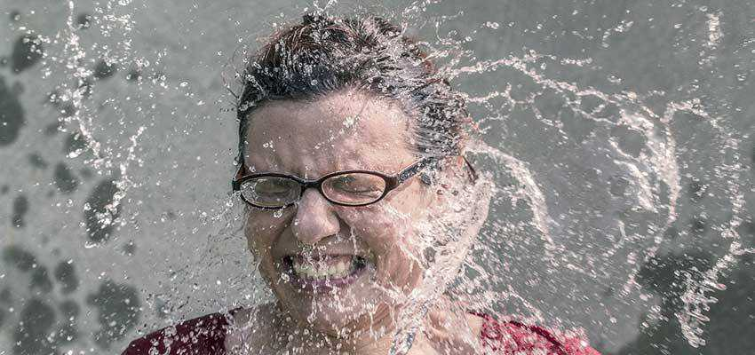 Woman being splashed with water.