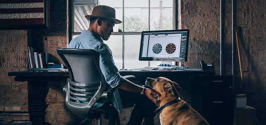 Man sitting at a computer, petting a dog.