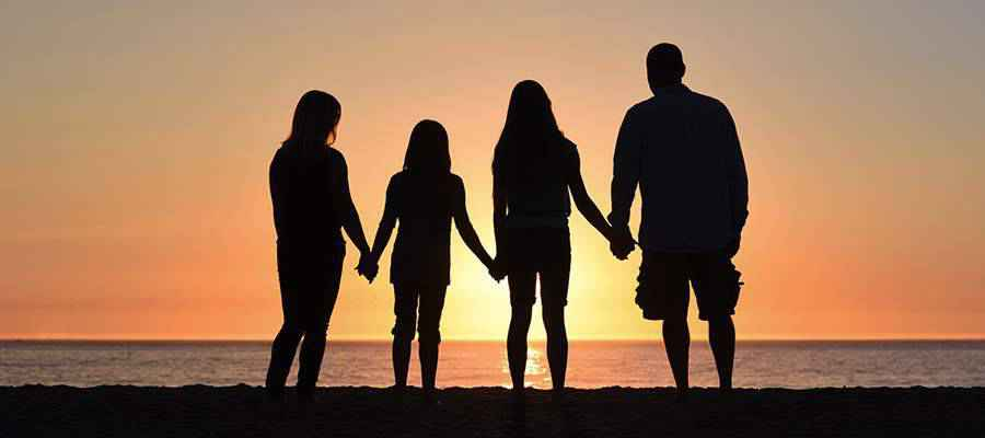 A family holding hands on the beach.
