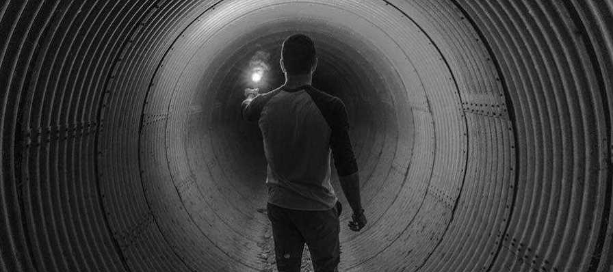A person holding a light in a dark tunnel.