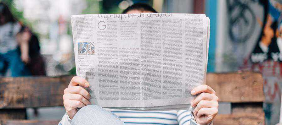 A person holding a newspaper.