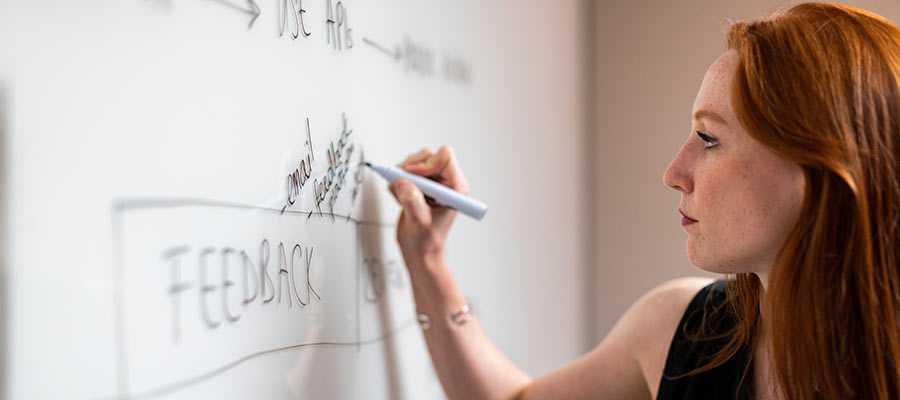 A woman writes on a white board.