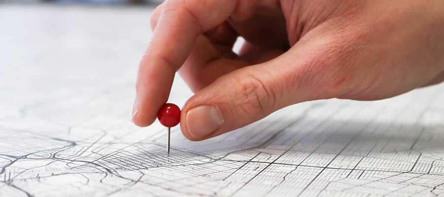 A person pushes a pin into a map.