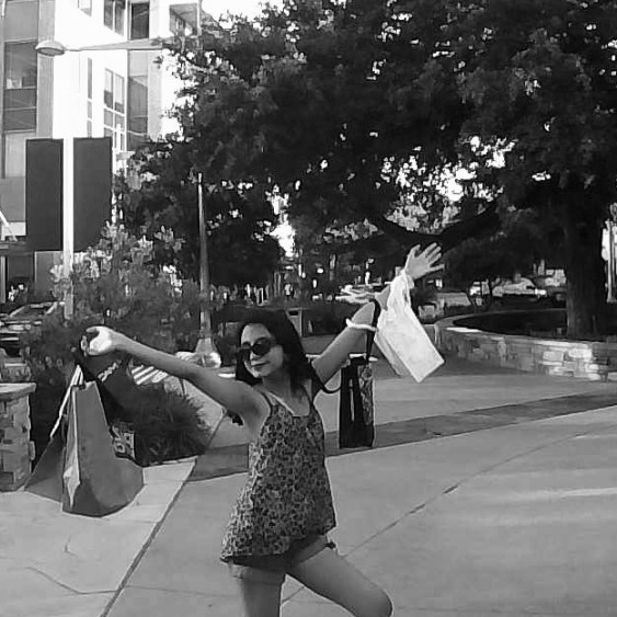 girl posing with shopping bags on arms at the domain in Austin, Texas.