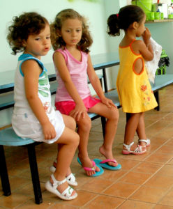 Three girls are shown to illustrate that echolalia can be an early sign of autism.