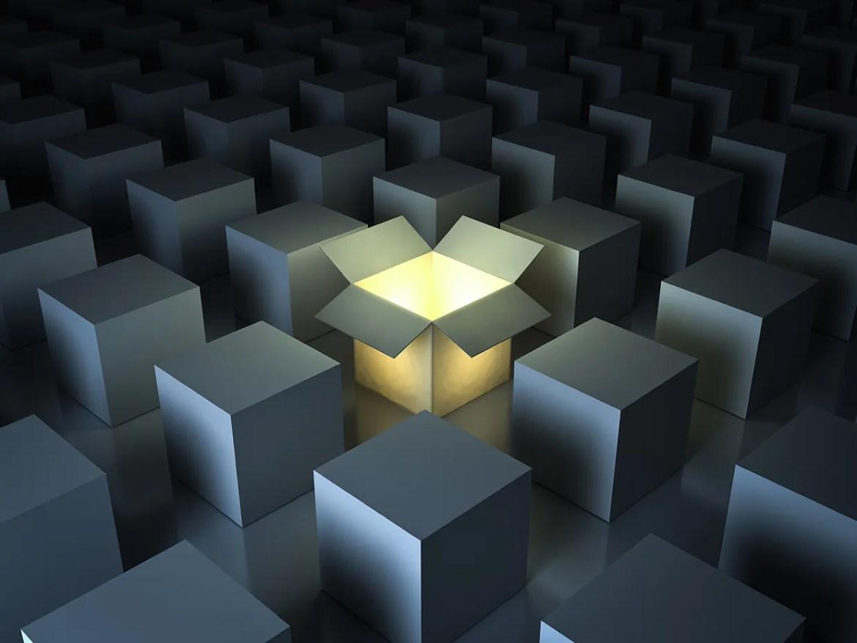 One luminous opened light box glowing among closed white square boxes on dark background