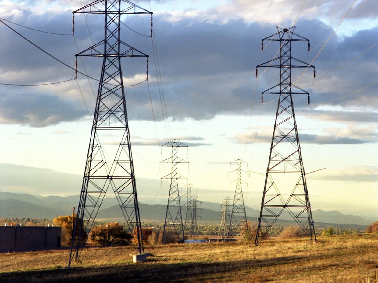hight resolution of a photo shows high voltage transmission lines crossing an open field