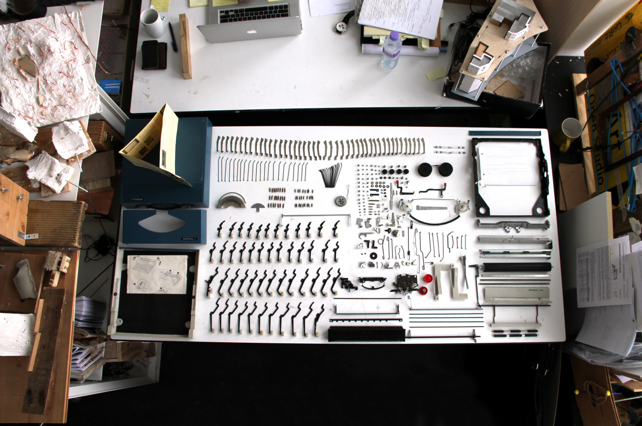 "Individual pieces of a typewrite laid out in neat geometric ""knolling"" pattern"