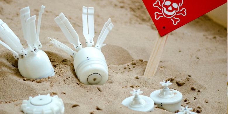 "3D printed mines laying in sand with a ""Danger Mines"" sign"
