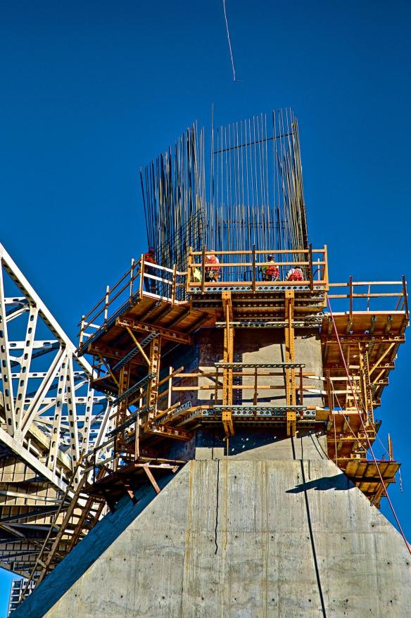 North tower, R-5, base with Ironworkers climbing and tying rebar. Sunny, cloudless, day with 3 people visible on scaffolding.