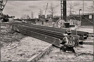 Carpenter/Pile Driver preparing beams for lifting into place on the pile driving engine. B&W Version