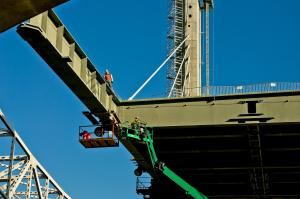 Ironworkers setting a floor beam for the downtown span #4